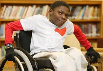Young male in wheelchair in library